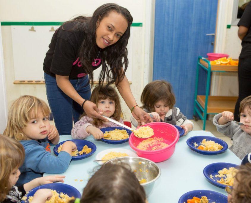 מטפלת מגישה אוכל לילדים